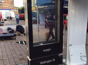 A digital advertising totem being erected in a town centre